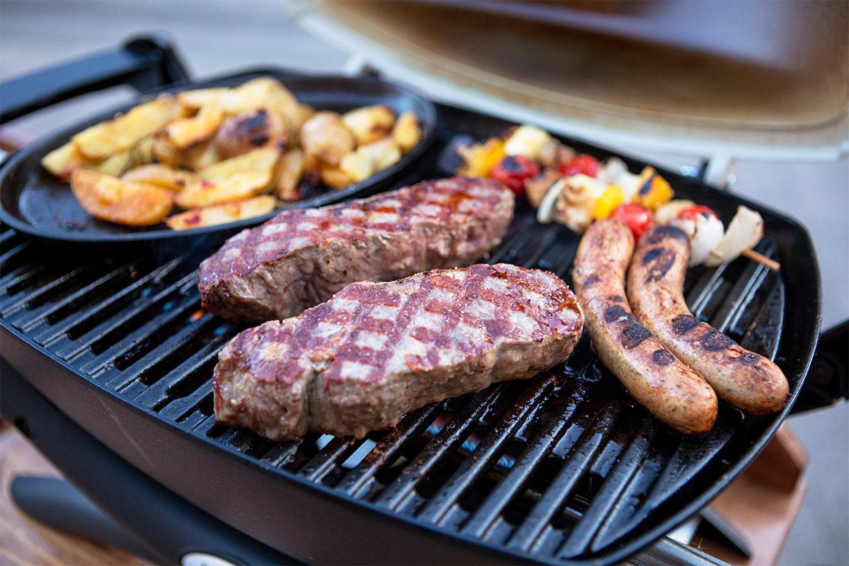 es liegen zwei Steaks, 2 Würstchen, 2 Grillspieße und Bratkartoffeln auf einem Grill.